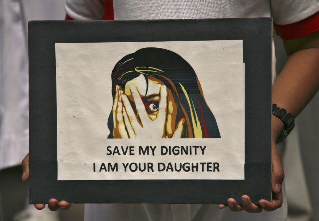 A schoolgirl holds a placard during a prayer meeting for a five-year-old rape victim in Jammu April 20, 2013. A five year-old girl was kept in captivity for 40 hours and allegedly raped and tortured in Delhi, police said, reviving memories of a brutal Dec