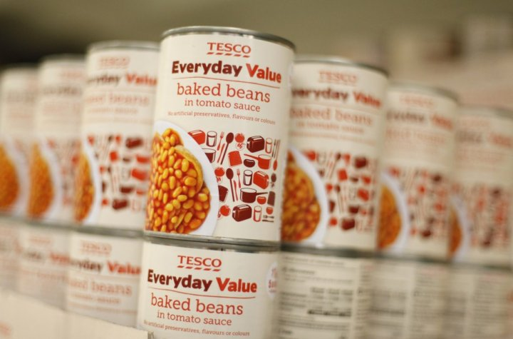 Tesco Everyday Value baked beans are stacked on a shelf at a Tesco shop in Bishop's Stortford, southern England