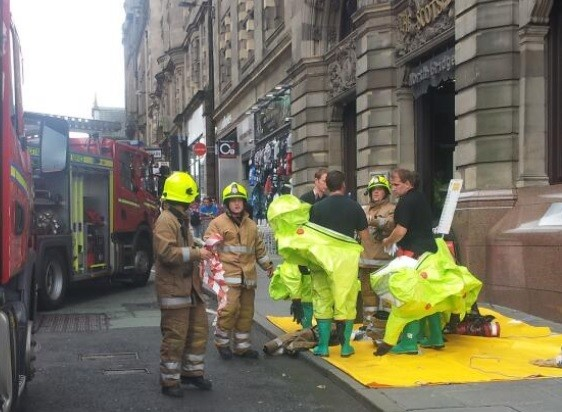 Fire-fighters wearing protective clothing outside Scotsman hotel
