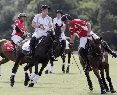 Prince Harry 2nd L and Prince William 2nd R compete in a charity polo match at Coworth Park, southern England August 3, 2013.
