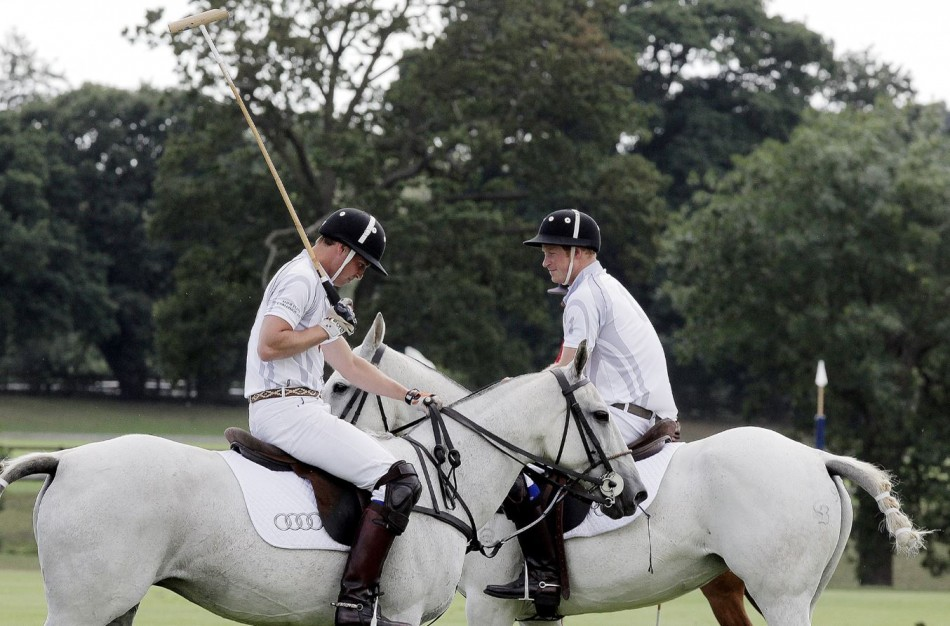Prince Harry R speaks to Prince William during a charity polo match at Coworth Park, southern England August 3, 2013.