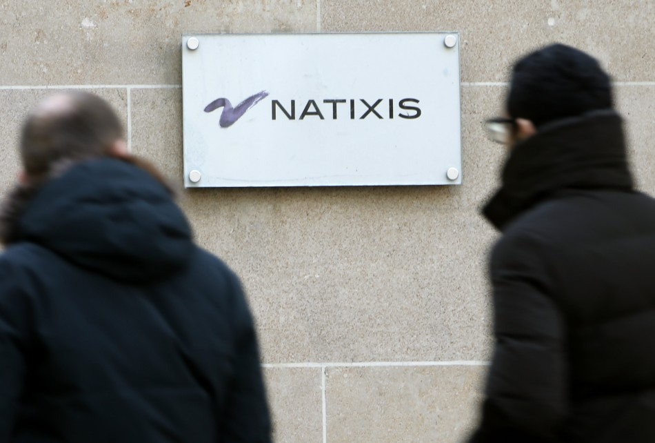 People walk past the logo of French bank Natixis at one of their office in Paris