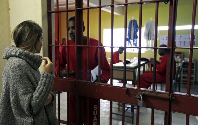 Brazilian fashion designer Raquel Guimaraes talks with a prisoner who knits for her. Guimaraes has given a hope to 18 prisoners to better their life; they were sentenced for crimes such as murder and armed robbery.(Photo: REUTERS/Paulo Whitaker)