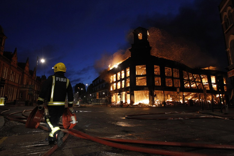 A firefighter walks past a burning building in Tottenham, north London August 7, 2011 (Photo: Reuters)