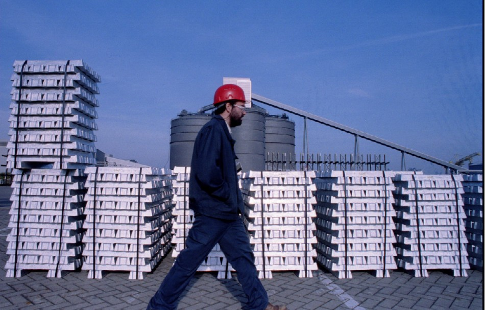A worker passes by stocks of aluminium ingot