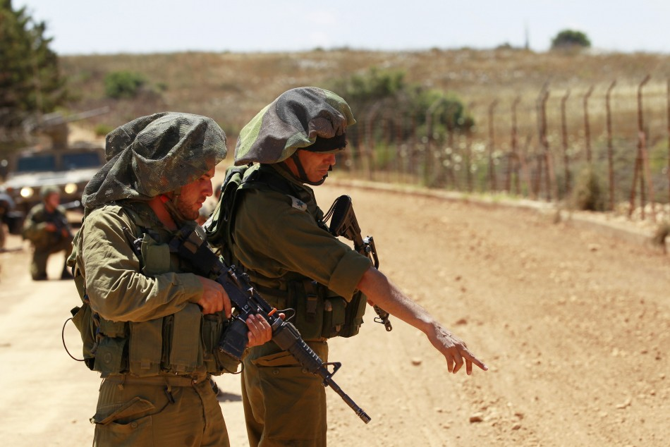 An Israeli army Lieutenant-Colonel (R) points as he stands with a another soldier during a patrol along Israel's border with Lebanon