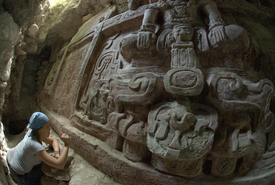 Archaeologist Anya Shetler cleans inscriptions on a Mayan Frieze unearthed in Holmul, Guatemala. The frieze is said to be the most spectacular frieze ever found in the region. (Photo: Estrada-Belli/© Holmul Archaeological Project)