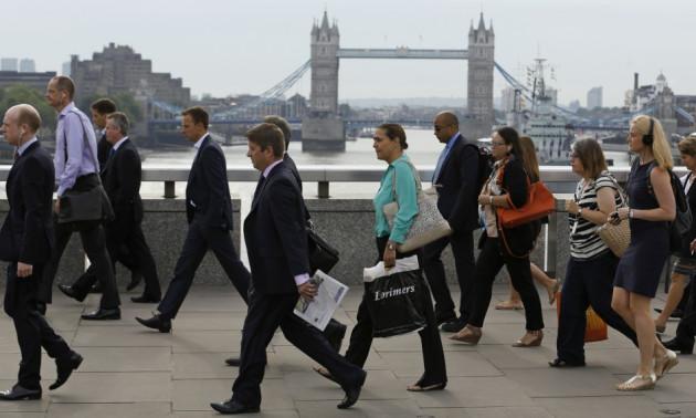 Commuters walk across London Bridge to the City of London