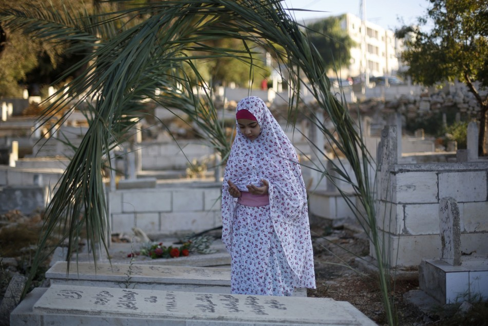 A Palestinian girl prays next to a grave at a cemetery in the West Bank city of Ramallah on the first day of Eid al-Fitr, August 8, 2013. (Photo:  REUTERS/Mohamad Torokman)