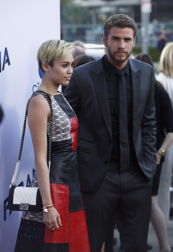 Liam Hemsworth poses with his fiancee, singer Miley Cyrus, at the premiere of