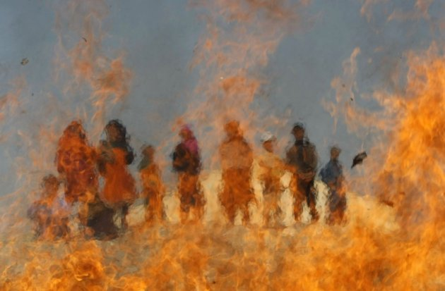 Afghan children watch burning expired medical items and food on the outskirts of Jalalabad, March 4, 2013. An Indian baby has been virtually in flames four times since his birth in May 2013 due to a rare condition called Spontaneous Human Combustion (Phot