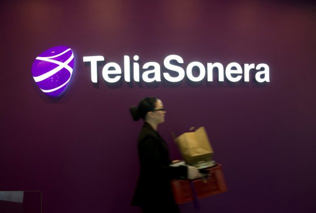 A woman walks past TeliaSonera's logo.
