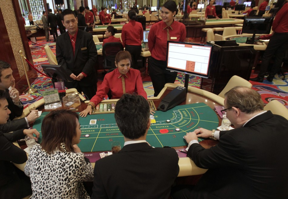 Foreigners play on a baccarat table during the opening of Solaire Casino-Resort in Pasay city.