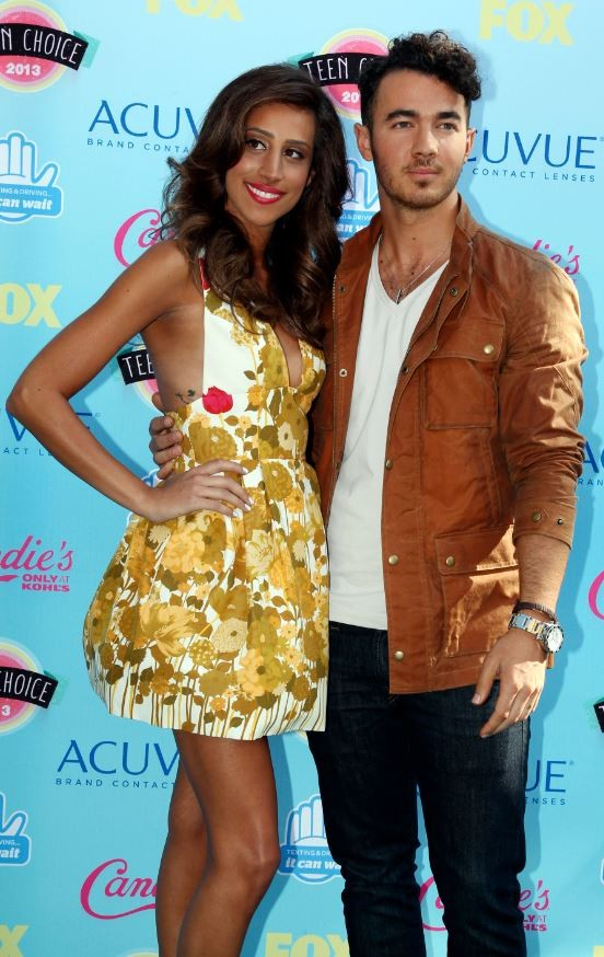 Singer Kevin Jonas and wife Danielle Deleasa pose as they arrive at the Teen Choice Awards at the Gibson amphitheatre in Universal City, California August 11, 2013.