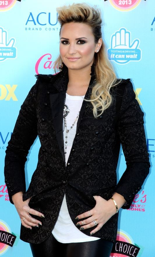 Singer Demi Lovato poses as she arrives at the Teen Choice Awards at the Gibson amphitheatre in Universal City, California August 11, 2013.