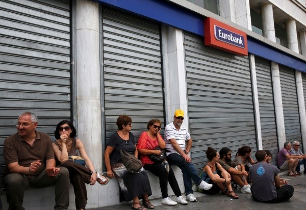 Anti-austerity protesters rest outside a closed bank during a rally in central Athens, Greece (Photo: Reuters)
