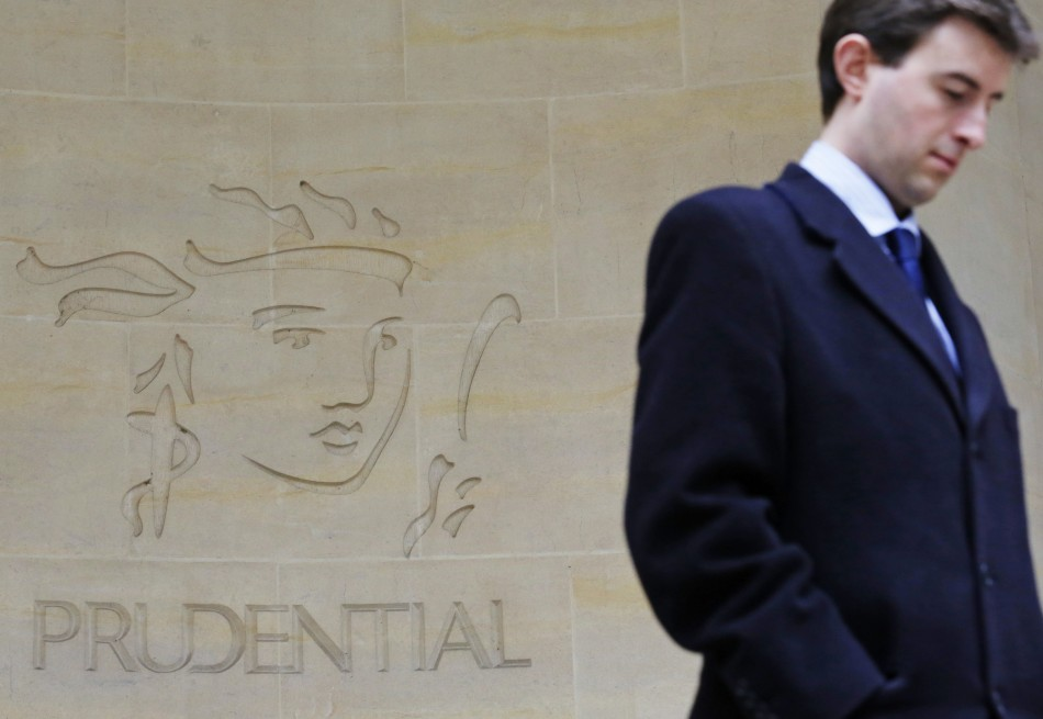 A man walks past a Prudential sign outside offices in the City of London
