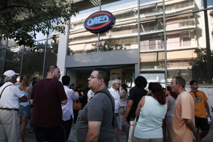 People wait outside a Greek Manpower Employment Organisation (OAED) office at Kalithea suburb in Athens.