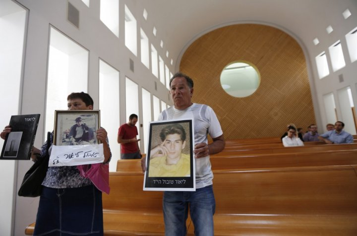 Miriam and Yaakov Tubol, parents of Lior, hold pictures of their son who was killed in 1990 by Palestinians, during a protest against the release of Palestinian prisoners