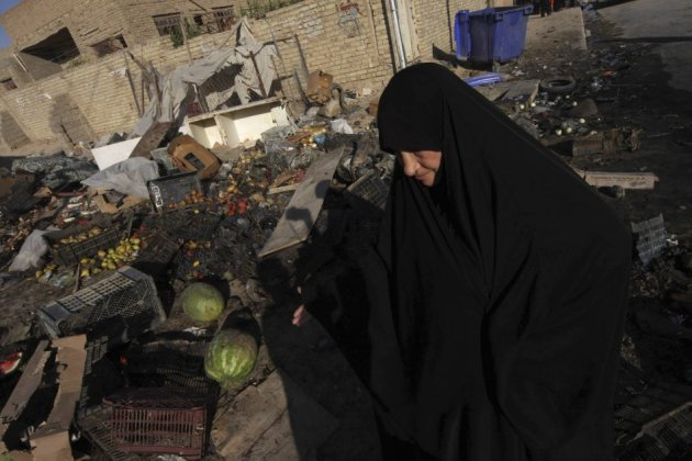 A woman walks past the site of a car bomb attack in Kerbala, 110 km (70 miles) south of Baghdad