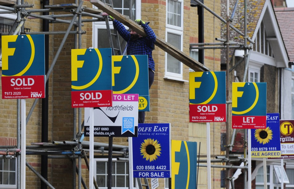 A man carries wood up scaffolding near For Sale and To-Let signs in west London