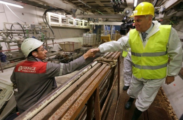French Prime Minister Jean-Marc Ayrault (R) shakes hands with an employee of Eiffage TP during a visit of a tunnel digging site in Velizy-Villacoublay, near Paris (Photo: Reuters)