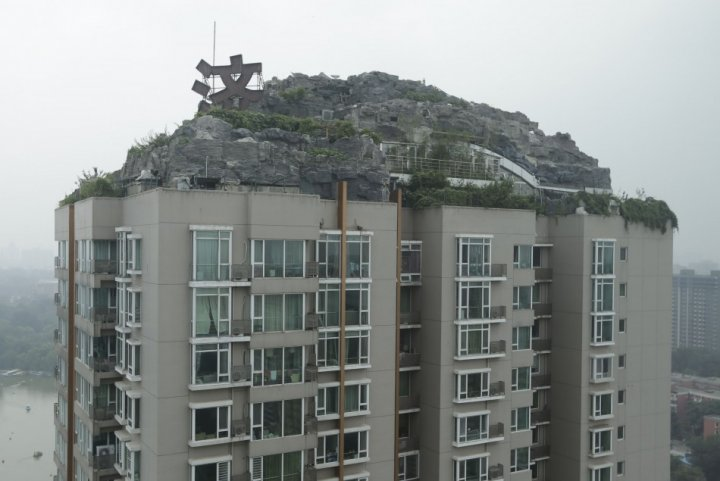 A privately built villa, surrounded by imitation rocks, on the rooftop of a 26-storey residential block in Beijing has sparked concerns over safety of the residents. (Photo: Reuters)