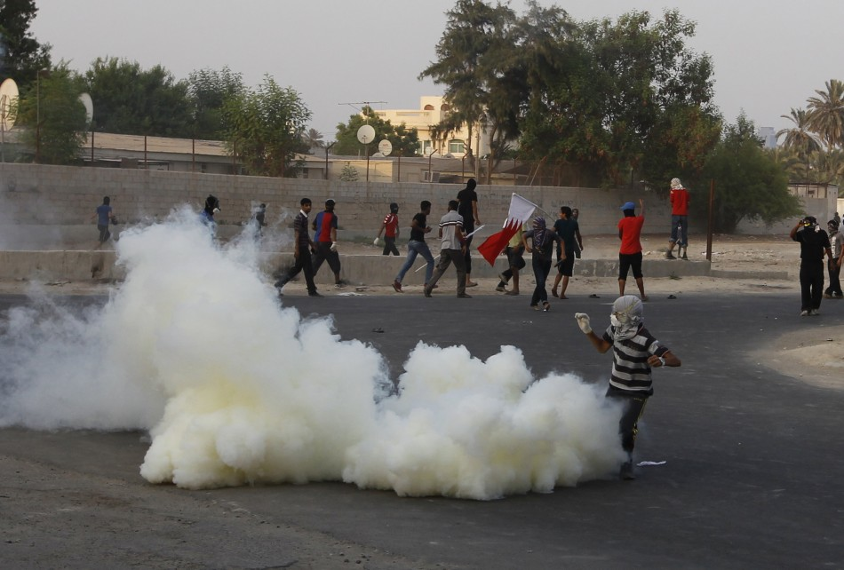 A protester is covered in a cloud of tear-gas during clashes with riot police in the village of Shakhoora, west of Manama,