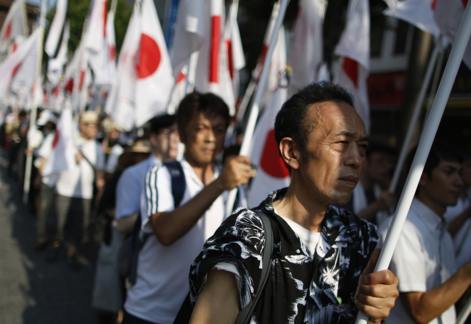 Nationalist Ganbare Nippon members march with Japanese flags in tribute at Yasukuni Shrine in Tokyo