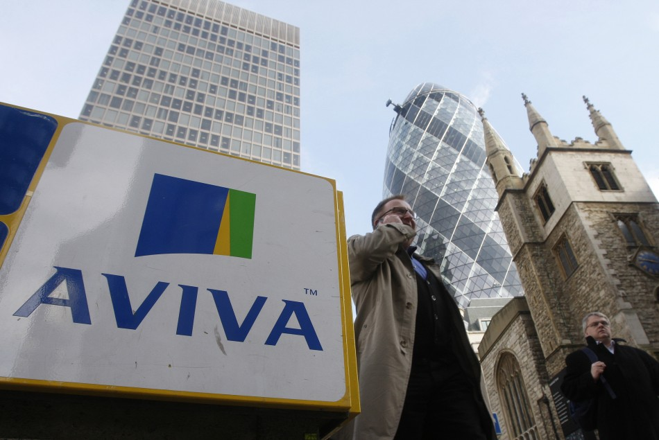Pedestrians walk past an Aviva logo outside the company's head office in the city of London.