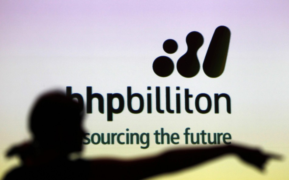A woman gestures in front of a BHP Billiton sign