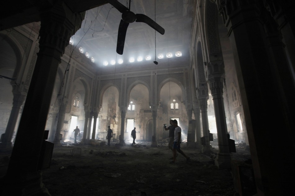 People walk inside the burnt Rabaa Adawiya mosque. (Photo: Reuters)