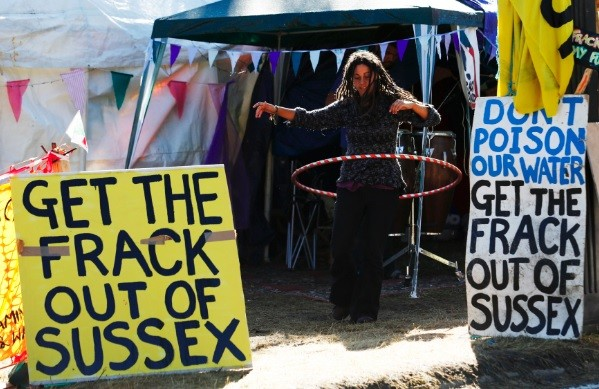 A demonstrator hula hoops among banners in the protest camp by the entrance to a site run by Cuadrilla Resources, outside the village of Balcombe in southern England (Photo: Reuters)