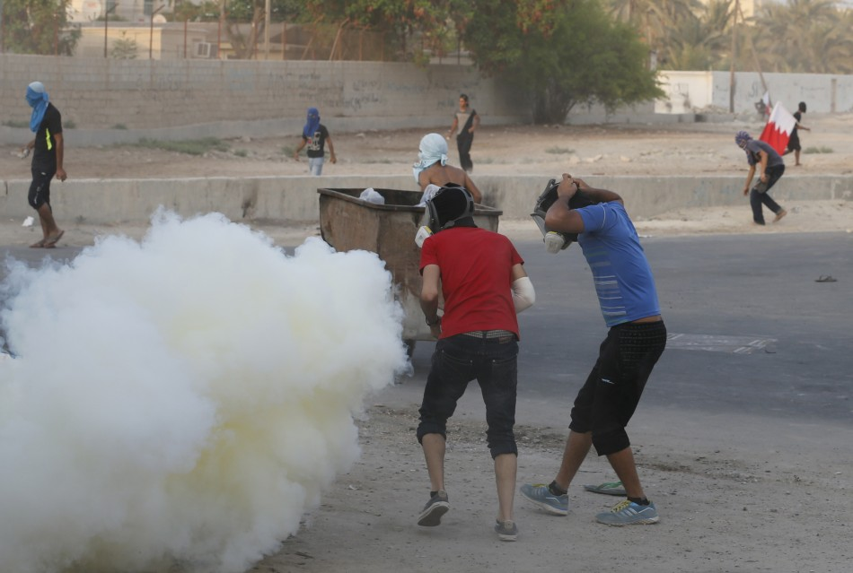 Protesters put on masks as riot police fire tear gas canisters at them during clashes in the village of Shakhoora