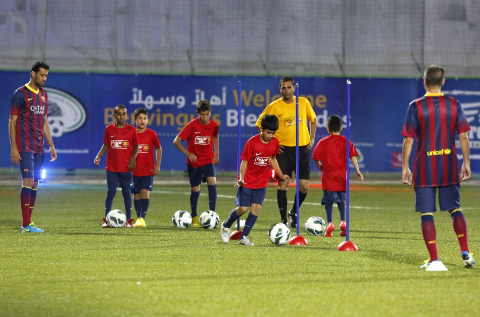 """Palestinian youth and FC Barcelona players take part in a """"soccer clinic"""" for peace, at Dura stadium in the West Bank village of Dura, near Hebron"""