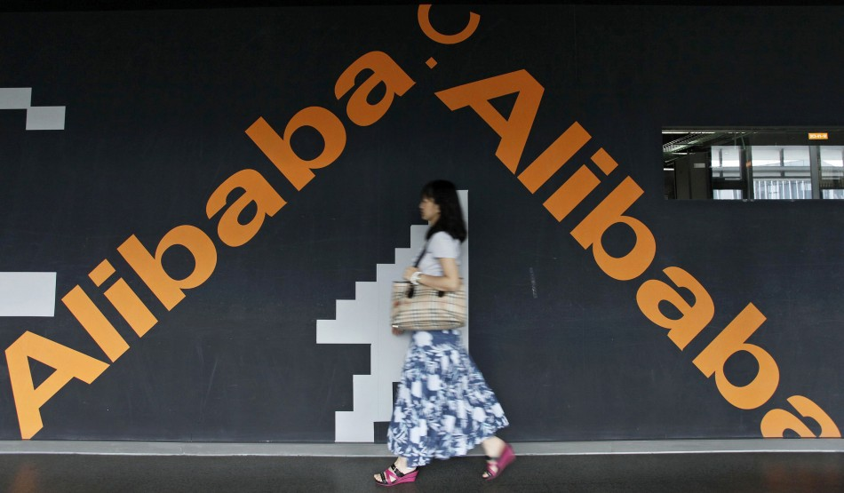 An employee walks past a wall painted with the logo of Alibaba (China) Technology.