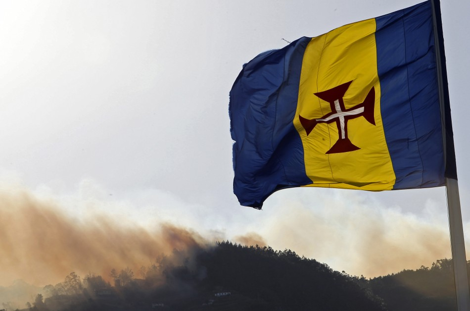 Fires rage in Madeira in July behind the regional flag.