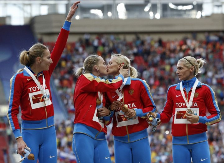 Gold medallists Kseniya Ryzhova and Tatyana Firova  kiss at the women's 4x400 metres relay victory ceremony during the IAAF World Athletics Championships at the Luzhniki stadium in Moscow
