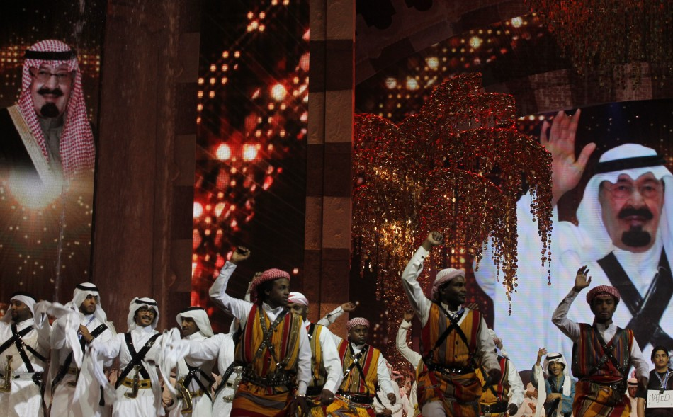 Performers raise their swords in front of a portrait of Saudi King Abdullah
