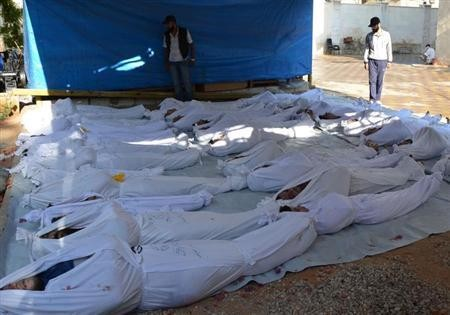 Syrian activists inspect the bodies of victims