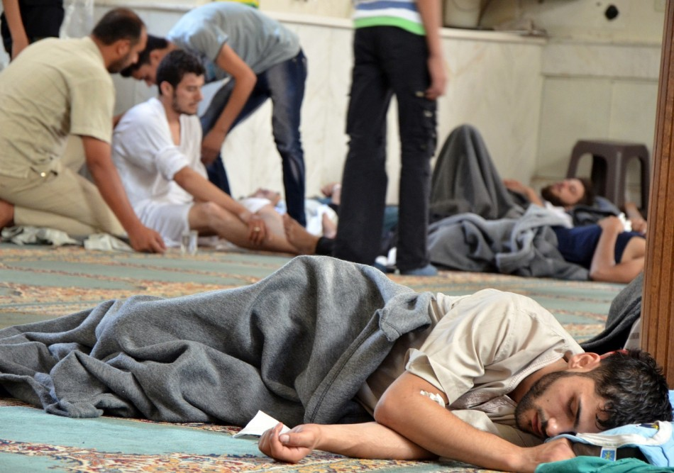 Survivors from what activists say is a gas attack rest inside a mosque in the Duma neighbourhood of Damascus