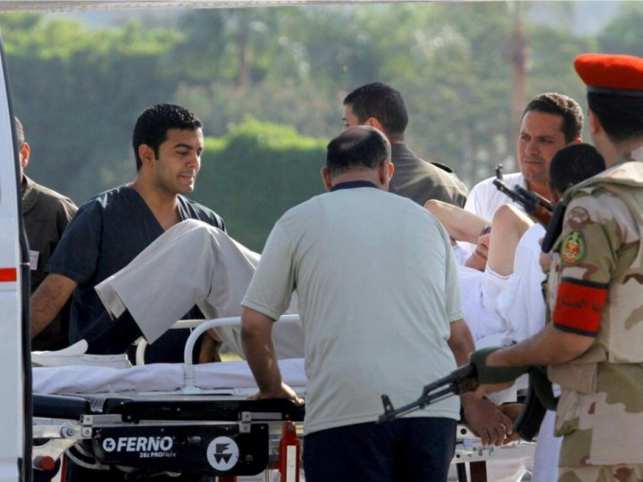 Mubarak helped into an ambulance after being flown to Maadi military hospital
