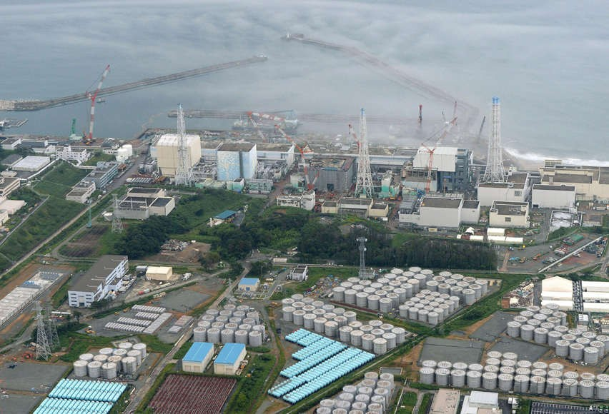 An aerial view shows Tokyo Electric Power Co.'s tsunami-crippled Fukushima Daiichi nuclear power plant and its contaminated water storage tanks, bottom, in Fukushima. Highly contaminated water has been found to be leaking from one of the hastily built con