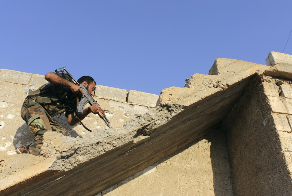 A Free Syrian Army fighter carries his weapon as he climbs on stairs