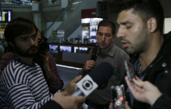 US journalist Glenn Greenwald (C) looks on as his partner David Miranda (R) talks with the media after arriving at Rio de Janeiro's International Airport August 19, 2013.