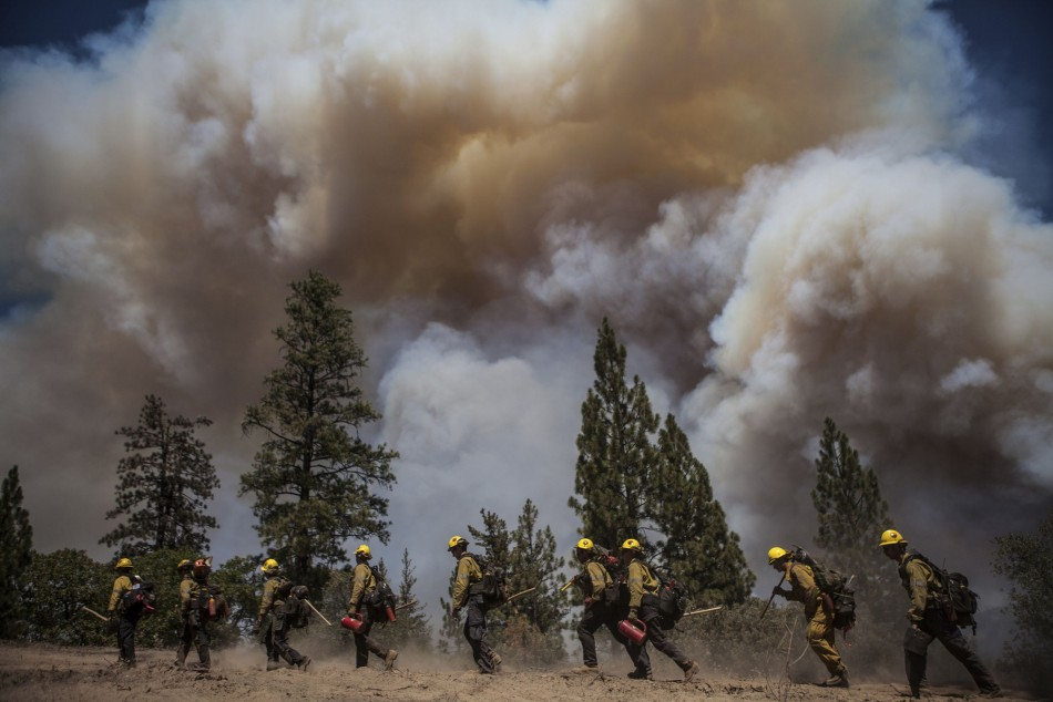 Los Angeles County firefighters hike in on a fire line on the Rim Fire near Groveland, California, August 22, 2013. The wildfire raging out of control near Yosemite National Park in northern California ballooned to nearly 54,000 acres on Thursday, more than tripling in size from the day before, forest officials said. (REUTERS/Max Whittaker)