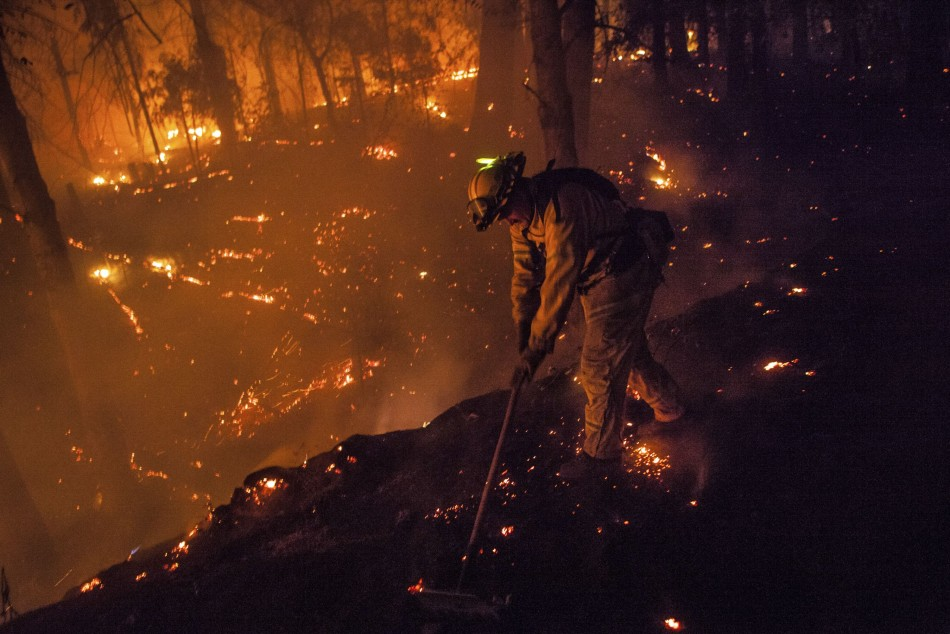 Firefighter Dave Beck rakes embers away from a road on the rim fire near Buck Meadows, California. (Photo: Reuters)