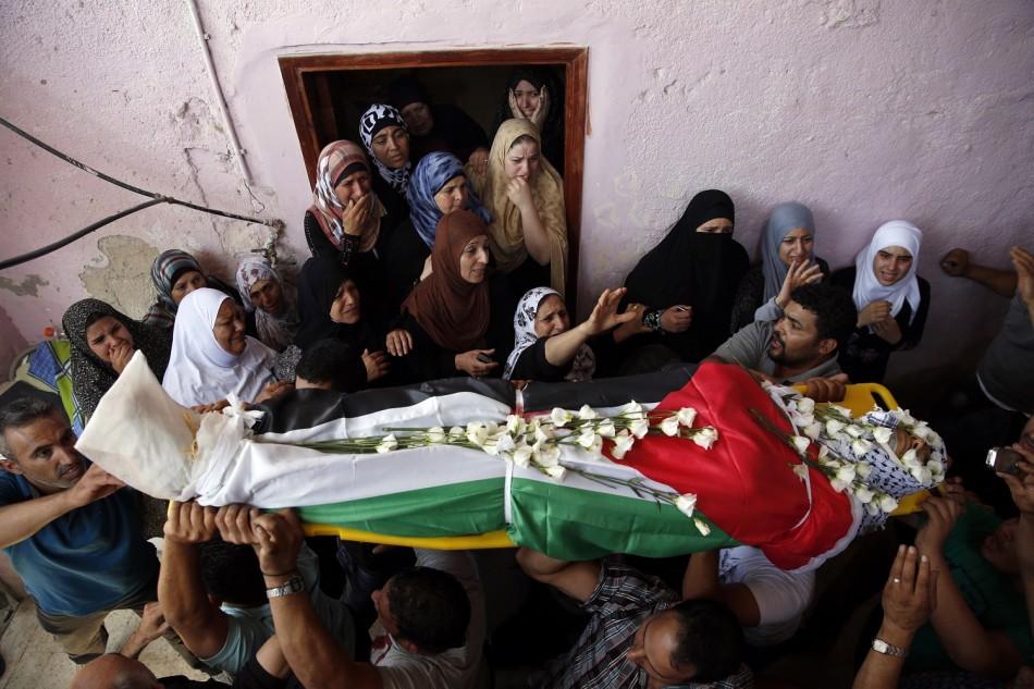 Palestinians carry the body of Jihad Aslan during his funeral at Qalandiya Refugee Camp near the West Bank city of Ramallah