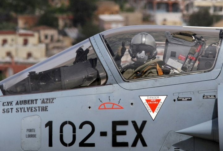 A French pilot gives a thumbs-up before taking off in a French Mirage 2000 fighter jet from the Greek air base at Souda