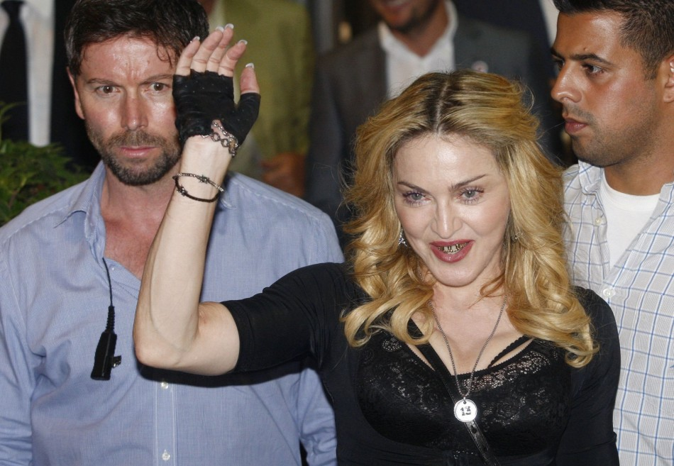 US singer Madonna waves as she leaves the new Hard Candy Fitness centre in downtown Rome August 21, 2013. Madonna is the top-earning celebrity in the world. (REUTERS/Remo Casilli)